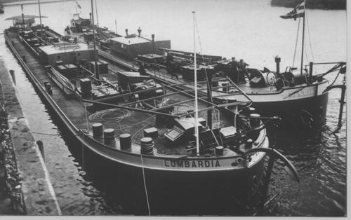 De sleeptankschepen LOMBARDIA en BELGIA bij elkaar opzij voor een sluis, ergens in België. Beide schepen zijn nog uitgerust met een open stuurbak en een pompkamer in de midscheeps.