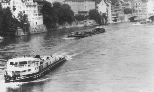 De motorsleepboot INTRITAS I, opvarend voor de stad van Basel. In aanhang twee geladen sleeptankschepen die bestemming Birsfelden hebben.