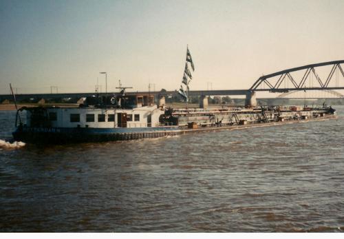 De ALSACIA, opvarend beneden Nijmegen. Er zijn een paar Van Ommeren vlaggen extra gehesen voor kapitein Henk de Haan die zijn laatste reis maakt en met de VUT mag. Foto: H. de Haan - met dank.