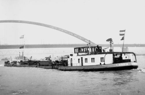 De AMISIA, opvarend beneden de brug van Hochfeld. Onder de brug zijn nog net de schoorstenen van een radersleepboot zichtbaar. Foto: Archief Arie Lentjes.