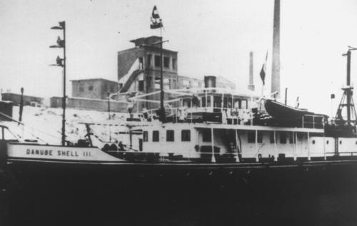 De motorsleepboot DANUBE SHELL III, kort na het einde van de Tweede Wereldoorlog voor de uitgebrande pakhuizen van Mannheim.