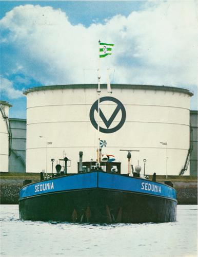 Het motortankschip SEDUNIA, gefotografeerd op het Calandkanaal met op de achtergrond een van de tanks van Matex Europoort.Deze foto is waarschijnlijk een montage want het Calandkanaal is op deze plaats niet geschikt om rond te gaan. Foto: Archief Van Ommeren - met dank.