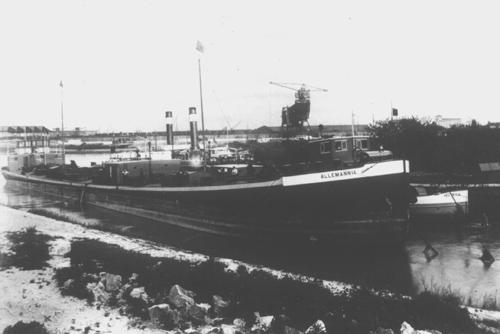 De tanksleepschepen ALLEMANNIA, MOSELIA en HELVETIA, liggende in de Alt-Rhein in Straatsburg. Voordat in Straatsburg de Petroleumhaven werd geopend (1926) was het de gewoonte om partijen gasolie en benzine voor Basel, vanuit grote sleepschepen over te slaan in kleinere schepen, die via de Rijn naar Basel konden. Op deze foto is de ALLEMANNIA gedeeltelijk leeggemaakt in de MOSELIA en HELVETIA. Aan de ankerketting van de ALLEMANNIA te zien ligt het schip er al een tijdje.