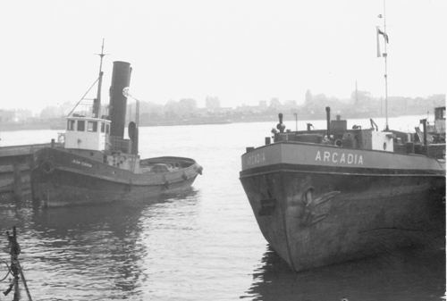 Het motortankschip ARCADIA, op een voor ons totaal onbekende bestemming. Helaas staat de ARCADIA niet geheel op de foto, maar vanwege de (waarschijnlijk) Franse sleepboot willen we deze foto toch graag plaatsen. Mocht iemand uitsluitsel over deze foto kunnen geven horen we het graag.