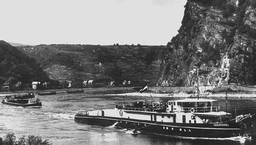 De motorsleepboot TREKVOGEL, met meerdere geladen sleeptankschepen in aanang, opvarend aan de Loreley