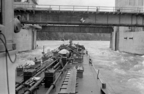 Het motortankschip ALBANIA passeert, met hulp van de voorspanboot VOGELGRIJFF, de in aanbouw zijnde stuw van Birsfelden.