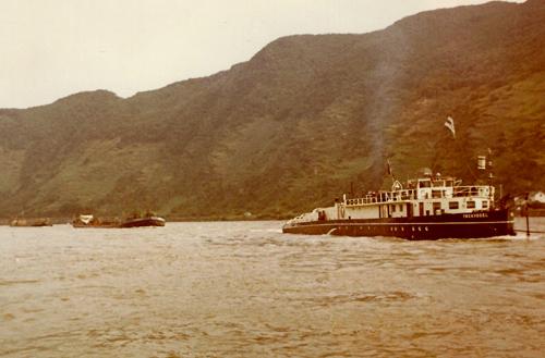 De motorsleepboot TREKVOGEL, met twee geladen sleeptankschepen, opvarend in het gebergte.