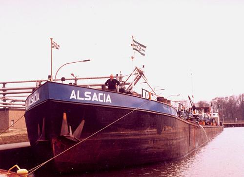 De ALSACIA in de haven van Rauxel/Castrop, op het Rhein-Hernekanaal (kmr. 41), na lossing bij de Teerverwaltung. Op het voorschip kapitein Henk de Haan.