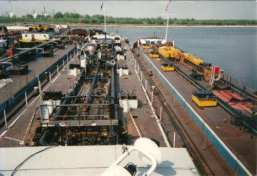 Het motortankschip SARINIA in afwachting van haar definitieve einde. Moerdijk was in de jaren negentig van de vorige eeuw nog niet het uitgestrekte industriegebied van vandaag de dag. Alleen Shell Moerdijk is zichtbaar in de verte.