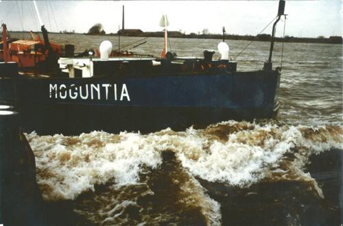 Ruim water op de Waal. De MOGUNTIA assisteert een ander motorschip de sterke stroom te overwinnen. Een mooie gelegenheid eens een foto van de kop (met forse snor) te maken. Foto: A. Vermeulen - Collectie Arie Lentjes.